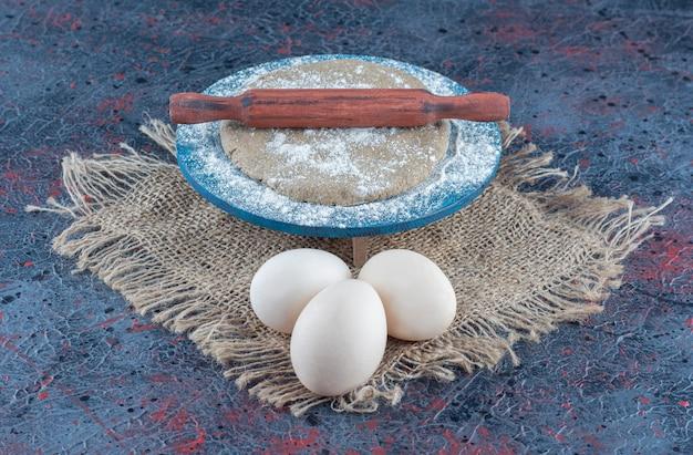 Drei ungekochte frische hühnereier mit teig auf einem sacktuch.