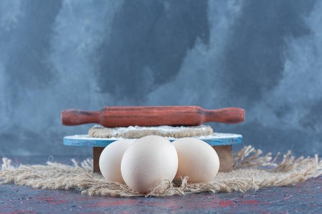 Drei ungekochte frische hühnereier mit teig auf einem sacktuch