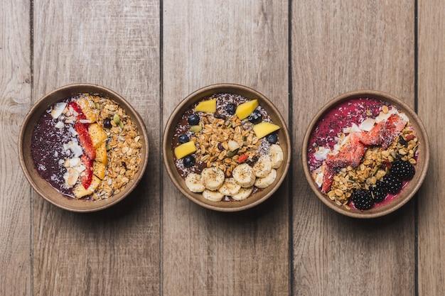 Drei vegane und gesunde desserts auf einem holztisch