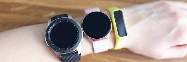 Drei verschiedene armbanduhren werden an der hand der frau getragen
