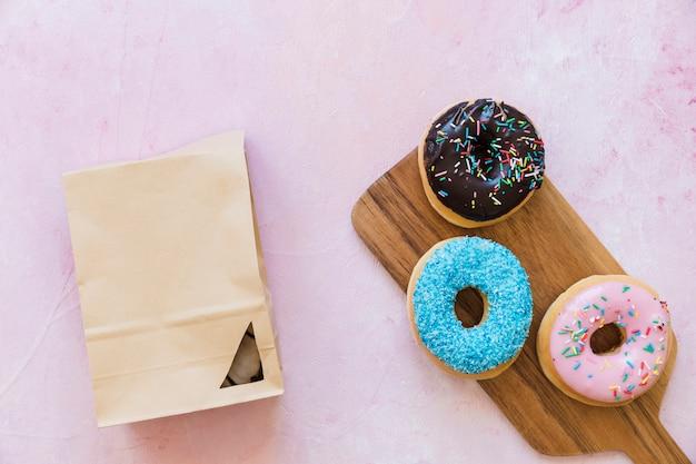 Drei verschiedene art von donuts in der nähe von paket auf rosa hintergrund