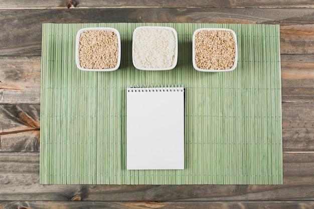 Drei verschiedene art von ungekochtem reis rollt mit gewundenem notizblock auf grünem placemat über der tabelle