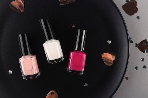 Drei verschiedene farben des nagellacks auf schwarzem teller unter herzformkonfetti