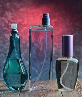 Drei verschiedene flaschen parfüm auf einem holzregal vor dem hintergrund einer betonwand. damenaccessoires für attraktivität. einladender duft.