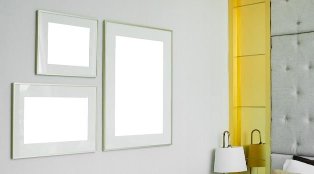 Drei verschiedene größen von leeren bilderrahmenmodellen auf weißem wandhintergrund im schlafzimmer