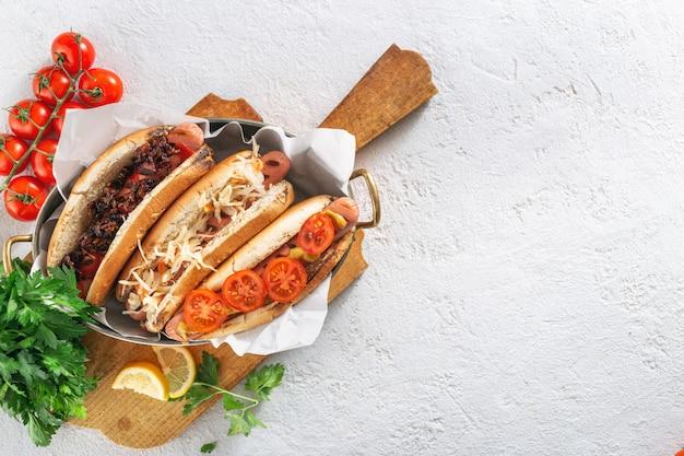 Drei verschiedene hot-dog-grills dienten in der pfanne auf einem holzbrett auf hellem hintergrund. kopieren sie die draufsicht auf den speicherplatz