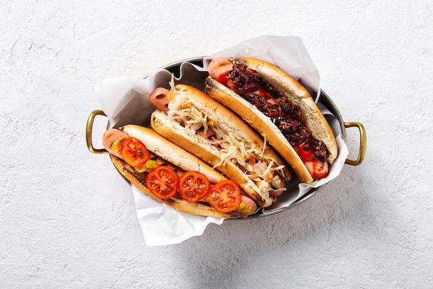 Drei verschiedene hot-dog-grills in einer pfanne auf hellem hintergrund, draufsicht