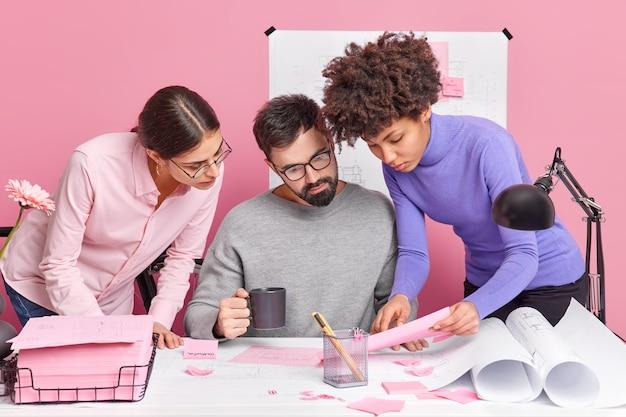Drei verschiedene kollegen arbeiten zusammen und haben ein brainstorming-meeting. schauen sie sich aufmerksam papiere an, posieren sie am schreibtisch mit skizzen, diskutieren sie ideen für eine produktive strategie und treffen sie sich im firmenbüro