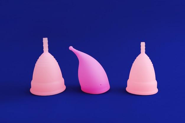 Drei verschiedene rosa wiederverwendbare silikon-menstruationstasse lokalisiert auf blau. konzept der frauenhygiene,