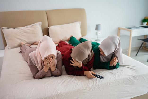 Drei verschleierte frau, die auf dem bett liegt und angst macht, wenn sie fernsieht