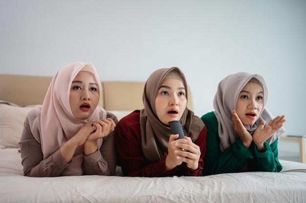 Drei verschleierte frauen, die auf dem bett liegen, genießen es, fernzusehen