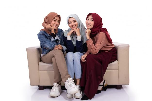Drei verschleierte frauen sitzen auf der couch, während sie in die kamera schauen