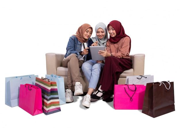 Drei verschleierte frauen, während sie in der nähe von papiertüten sitzen und kreditkarte halten, um in einem online-shop zu kaufen