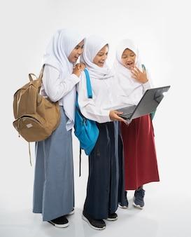Drei verschleierte mädchen in schuluniform, die gemeinsam einen laptop benutzen, während sie einen rucksack tragen...