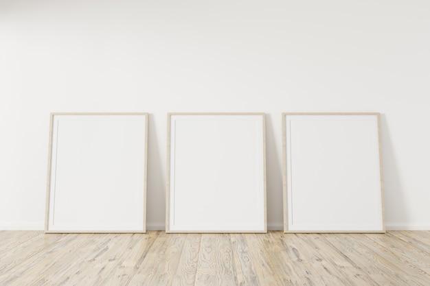 Drei vertikale holzrahmenplakat auf holzboden mit weißer wand