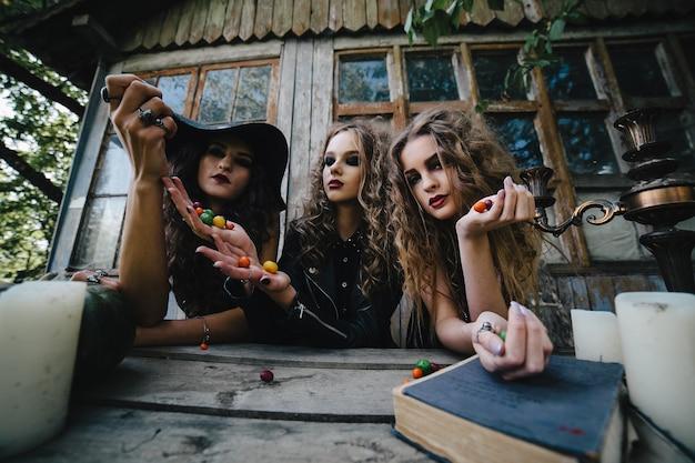 Drei vintage-hexen führen ein magisches ritual durch und werfen am vorabend von halloween süßigkeiten auf einen tisch