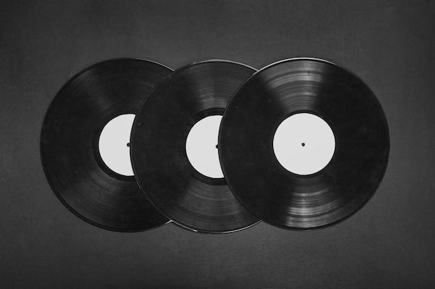 Drei vinyl-schallplatten auf schwarzem hintergrund