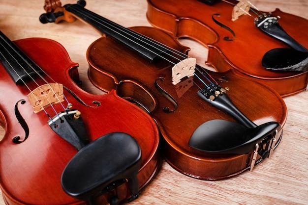 Drei violinen setzen auf holzbrett, weinlese und kunstton