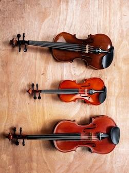 Drei violinen setzen auf holzbrett