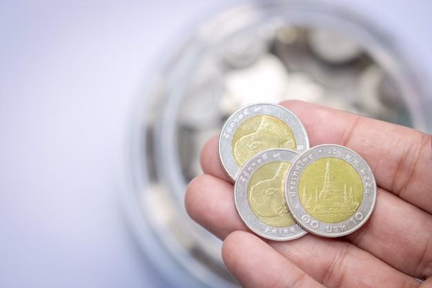 Drei von zehn-baht-goldsilbermünzen an hand mit glasflaschenmünzen