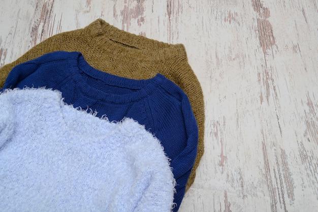 Drei warme pullover auf einer hellen holzoberfläche