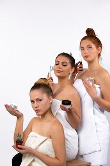 Drei weibliche modelle mit spa- und wellnesskosmetik nahe natürlichen blumen, die in einer pyramidenform auf weißer wand aufwerfen