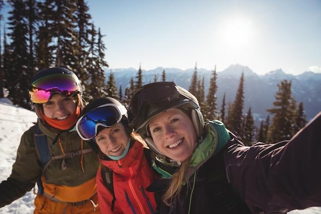 Drei weibliche skifahrer, die zusammen auf schneebedecktem berg stehen