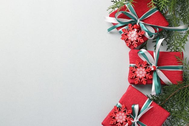 Drei weihnachtsgeschenke in rotem papier mit bändern auf weißer oberfläche. weihnachtsferiengeschenke. weihnachtskarte. copyspace