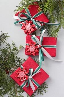 Drei weihnachtsgeschenke in rotem papier mit schneeflocken und bändern auf heller oberfläche. weihnachtsferiengeschenke. vertikales format. draufsicht
