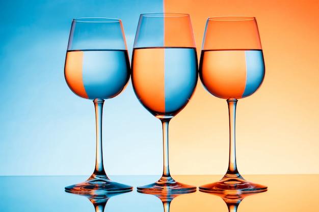 Drei weingläser mit wasser über der blauen und orangefarbenen wand