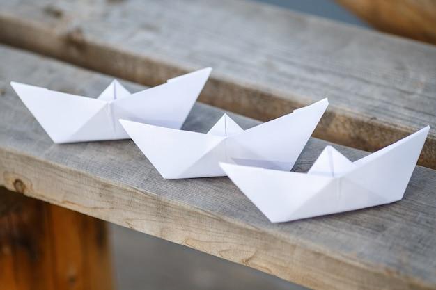 Drei weißbuchboote auf holzbank