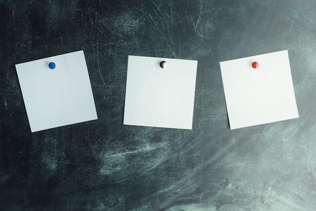 Drei weiße aufkleber auf dunklem brett