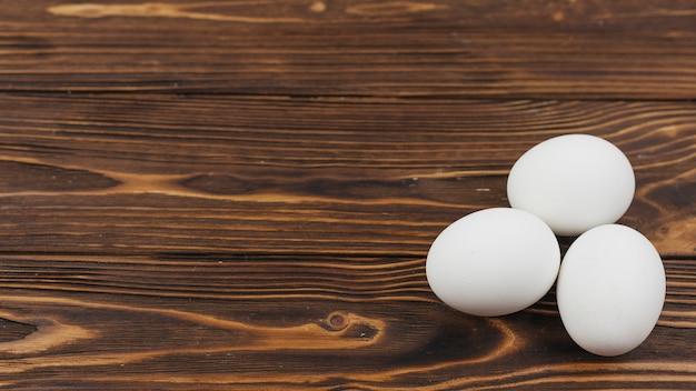 Drei weiße eier auf holztisch