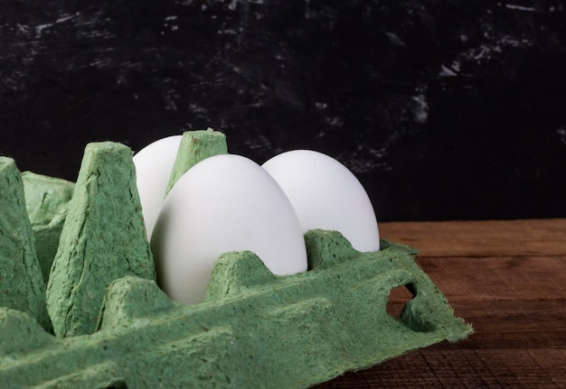 Drei weiße hühnereier in einem grünen behälter auf einem braunen holztisch.