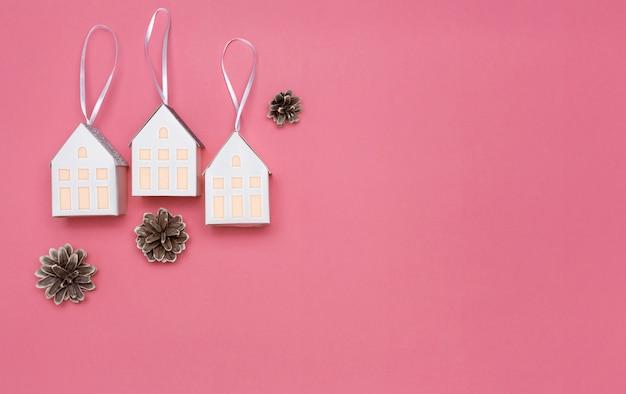 Drei weiße papierhäuser auf einem rosa hintergrund. kopieren sie platz. ansicht von oben. neues jahr-konzept.