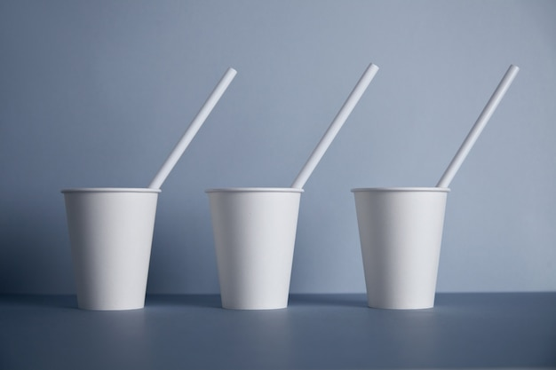 Drei weiße pappbecher ohne verschluss zum mitnehmen mit trinkhalmen in der mitte