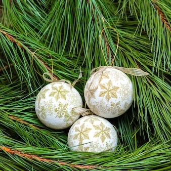 Drei weiße weihnachtskugeln auf einem weihnachtsbaum