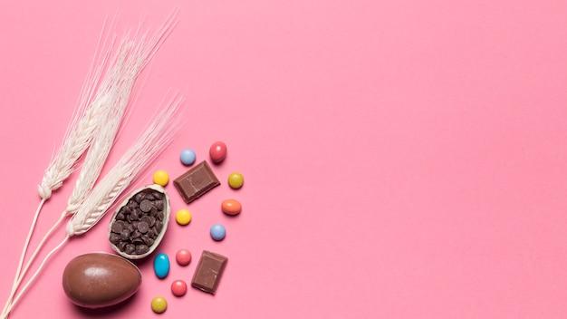 Drei weizenähren mit schokoladen-ostereiern und edelstein-süßigkeiten auf rosa hintergrund