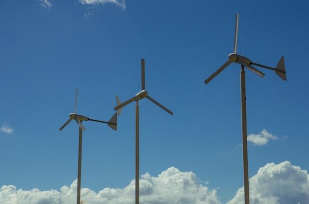 Drei windturbinen mit blauem himmel