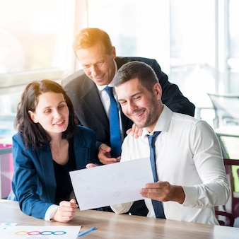 Drei wirtschaftler, die geschäftsbericht im büro betrachten