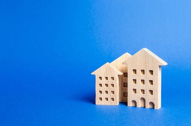 Drei wohngebäude figur das konzept des kaufs und verkaufs von immobilien vermietung suche nach einem mehrfamilienhaus