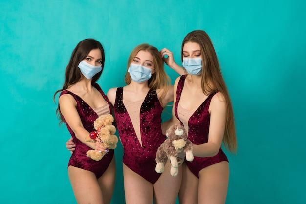Drei wunderschöne frauen in schneemädchenkostümen lächeln und schreien in schutzmaske an der blauen wand