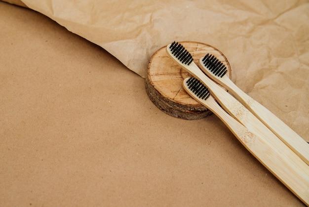 Drei zahnbürsten aus natürlichem bambus liegen auf einem stück holz vor einem hintergrund aus braunem kraftpapier. ein nachhaltiger lebensstil und ein plastikfreies konzept, bad essentials.