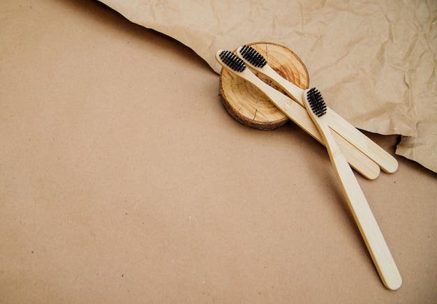 Drei zahnbürsten aus natürlichem bambus liegen auf einem stück holz vor einem hintergrund aus braunem kraftpapier.