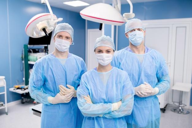 Drei zeitgenössische profis in schutzmasken, handschuhen und uniform