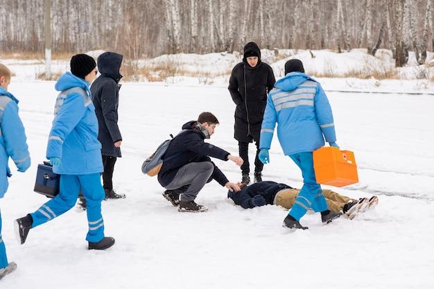 Drei zeitgenössische sanitäter in blauer uniform eilen zu einer kranken person, die im schnee liegt, während zwei männer neben ihm stehen