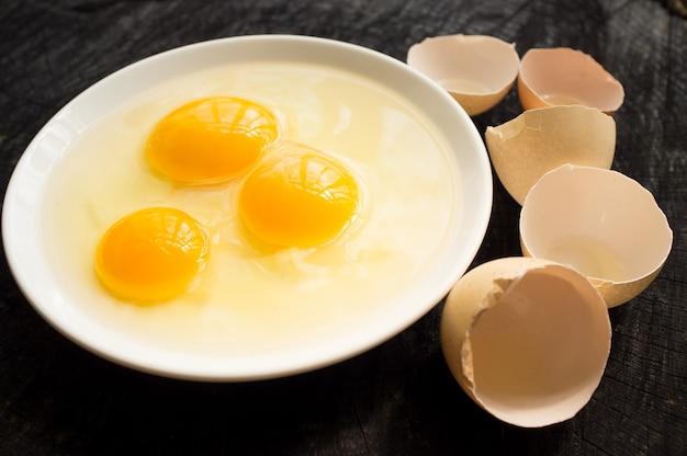 Drei zerbrochene eier und zerbrochene schale auf dunklem holzschreibtisch