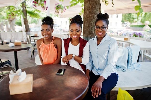 Drei zufällige afroamerikanermädchen mit dem farbigen einkaufstaschegehen im freien. der einkauf der stilvollen schwarzen frau.