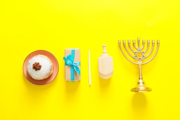 Dreidel und donut für chanukka mit menora und geschenk auf farbhintergrund