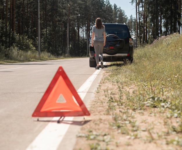 Dreieck vorsicht schild nahaufnahme auf der straße mit junge frau geht zum auto im hintergrund warten auf auftauchen...